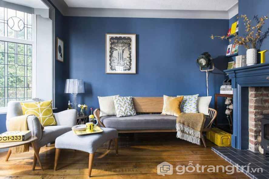 Căn phòng khách này được lát sàn gỗ với mảng tường màu xanh đậm (Ảnh: Internet)