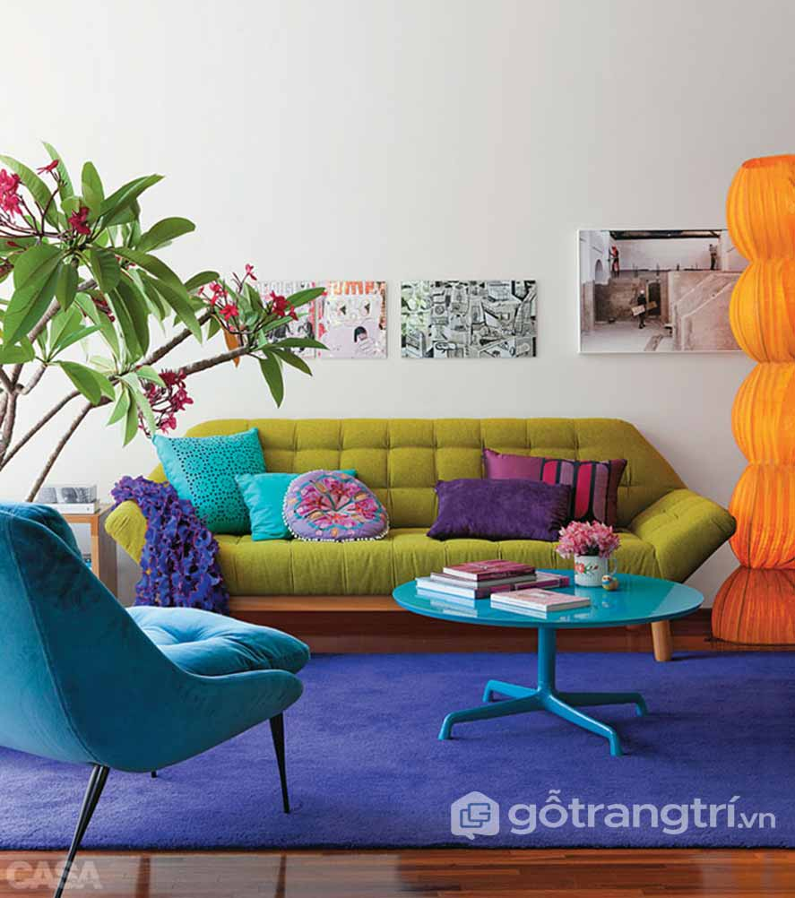 Bức tường màu xám làm nổi bật cho ghế sofa màu xanh là , xanh dương và đồ trang trí nhiều sắc màu nổi bật (Ảnh: Internet)