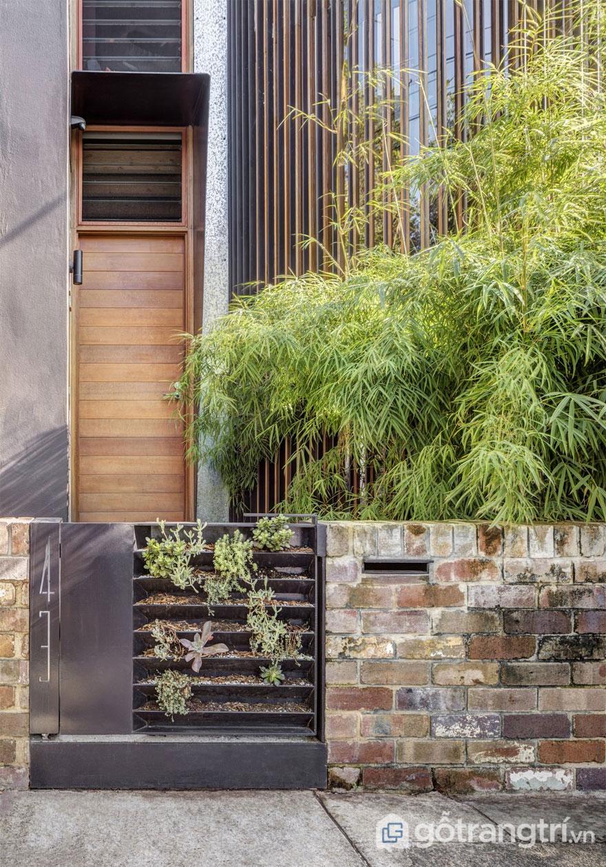 Mặt tiền ngôi nhà đã thể hiện được kiến trúc xanh - một ngôi nhà với ngập tràn cây cối, gạch thô - Ảnh: Murray Fredericks