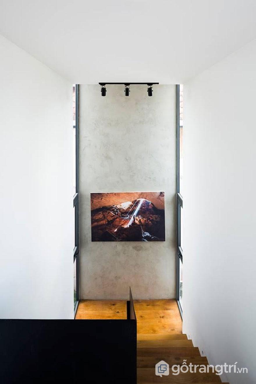 Bức tranh nghệ thuật được treo khá thấp so với chiều cao bức tường làm điểm nhấn cho ngôi nhà theo kiến trúc hiện đại - Ảnh: Hiroyuki Oki