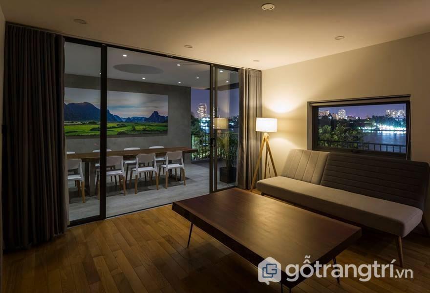 Tông màu trầm chủ đạo của không gian đã gắn kết với chất liệu gỗ mộc mạc từ bàn trà, hay sàn nhà làm nổi bật lên kiến trúc hiện đại của Thủ Đức House - Ảnh: Hiroyuki Oki