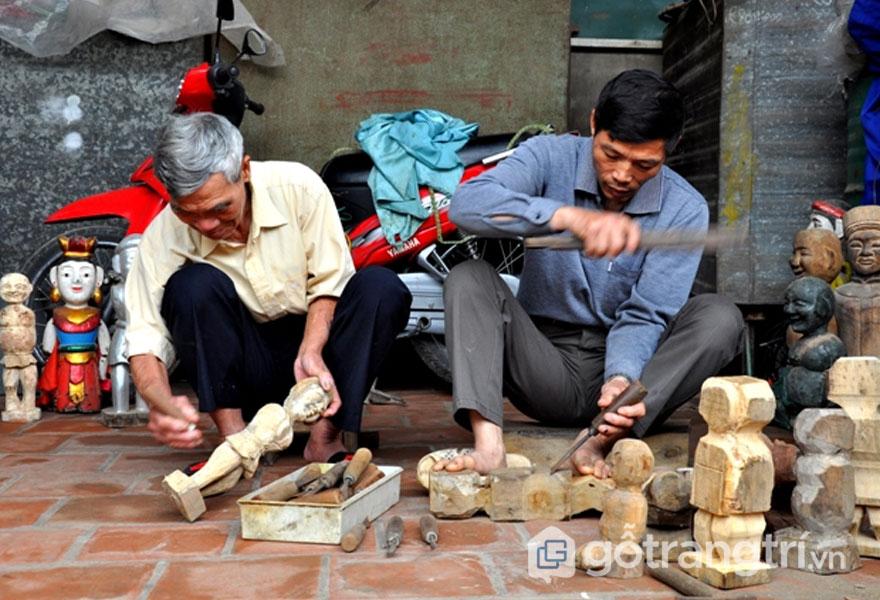 Nghệ nhân làng nghề đang tạo hình chú rối nước bằng gỗ sung - Ảnh: Internet