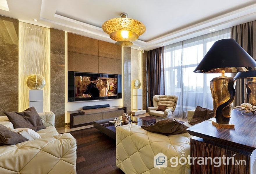 Thiết kế Art Deco của phòng khách nổi bật hơn khi sử dụng đá cẩm thạch ốp tường, và sàn gỗ màu nâu (Ảnh: Internet)