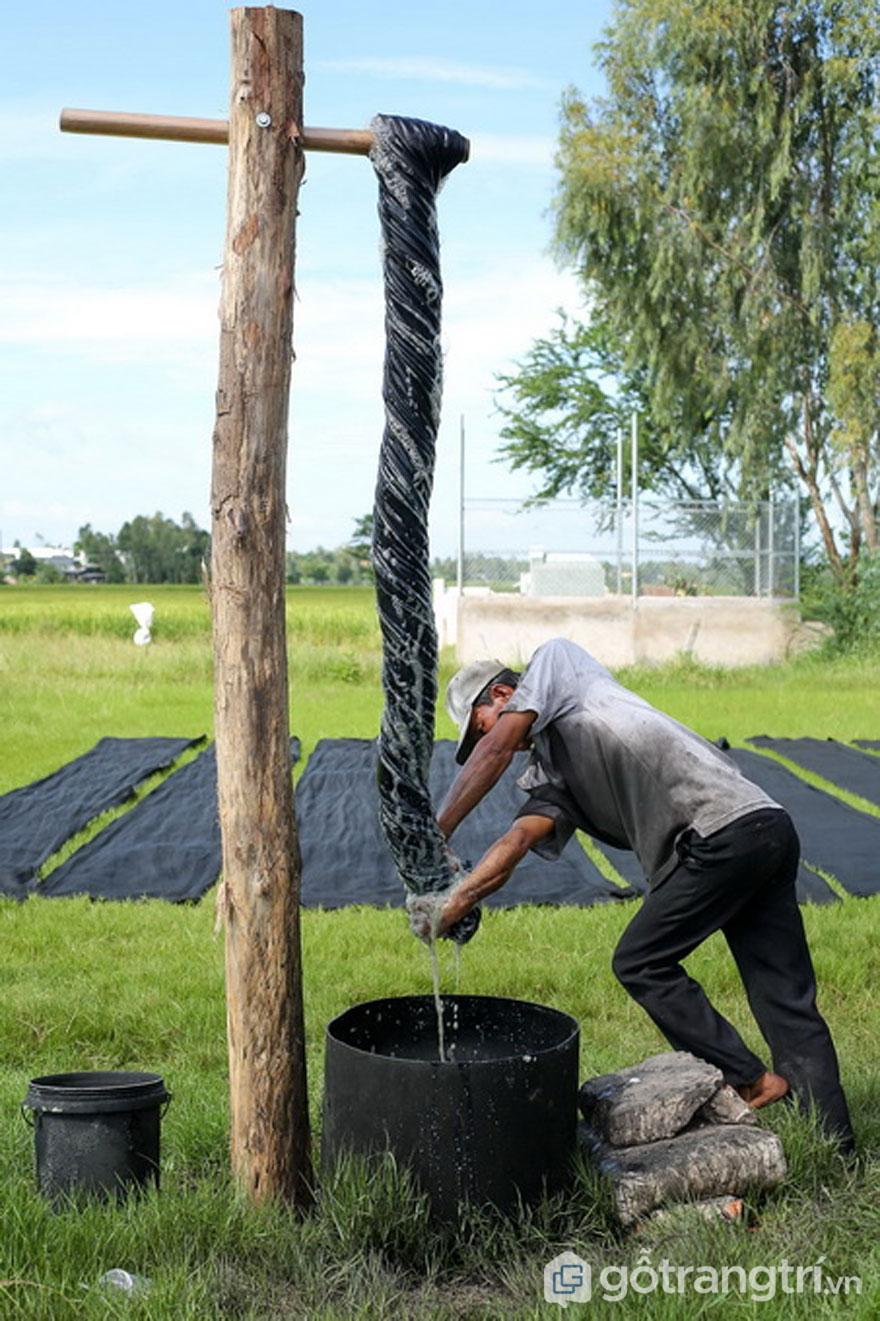 Người thợ dùng hết công sức để vắt lụa sạch nước (Ảnh: Internet)