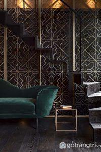 Họa tiết lưới mắt cáo màu vàng kim loại trên tường được thiết kế theo phong cách Art Deco sang trọng. Chiếc ghế sofa màu xanh lá đậm nổi bật trong căn phòng tối - Ảnh internet
