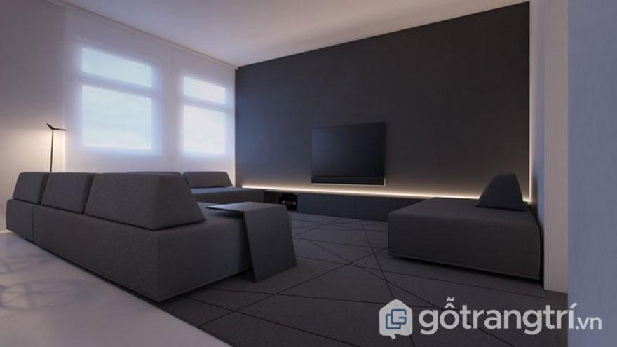 Màu đen huyền bí của chiếc ghế sofa hiện đại cùng với tấm thảm trải sàn có họa tiết đa giác bắt mắt khi được chiếu sáng bởi hệ thống đèn trang trí dưới tivi tạo không gian sang trọng (Ảnh: Internet)