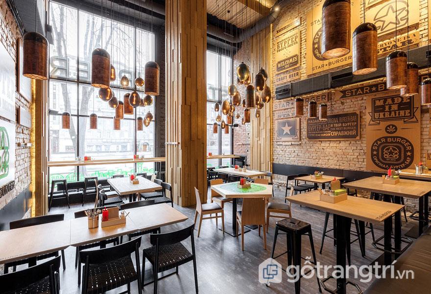 Nhà hàng bài trí theo phong cách thiết kế công nghiệp với đèn treo thả trần, cột gỗ và mặt bàn là bằng gỗ, khung và chân, ghế ngồi được làm từ kim loại nhìn rất thanh thoát (Ảnh: Internet)
