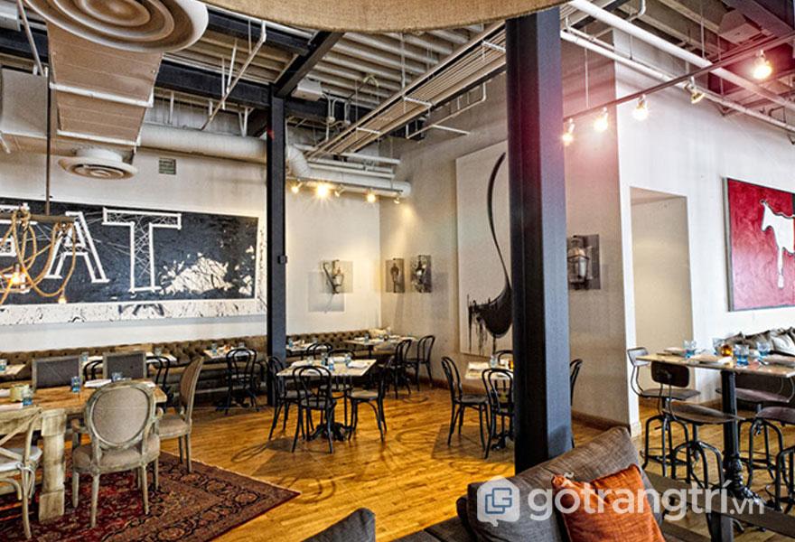 Sàn nhà hàng được lát bằng gỗ, sử dụng tấm thảm trải hoa văn nhẹ nhàng. Trần nhà để lộ đường ống dẫn tạo sự mới lạ (Ảnh: Internet)