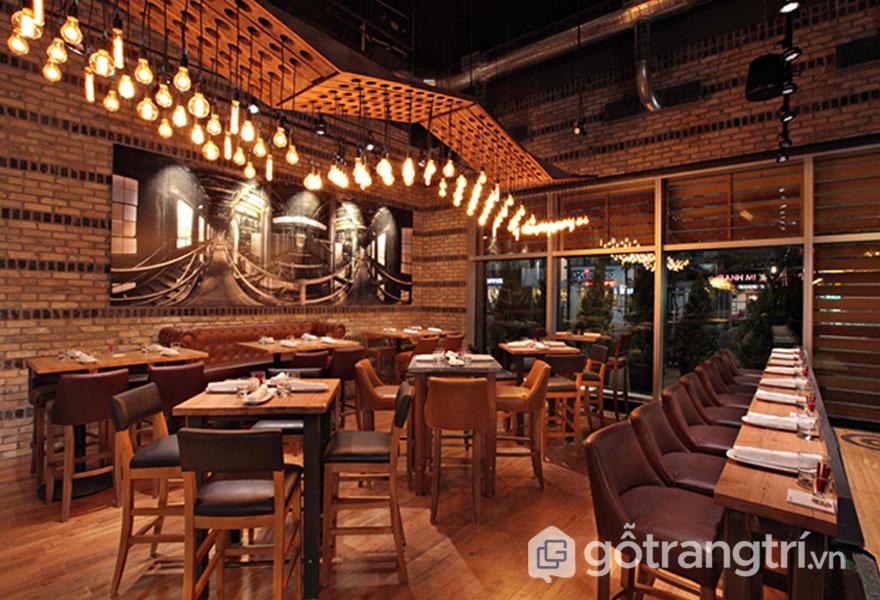 Nhà hàng công nghiệp này nổi bật với mảng tường gạch thô và dải đèn trang trí tạo được sự ấm cúng, thân thương (Ảnh: Internet)