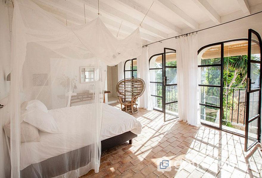 Phòng ngủ trang trí rèm cửa sổ và rèm che giường đều bằng vải voan kết hợp gạch nung cỡ nhỏ (Ảnh: Internet)
