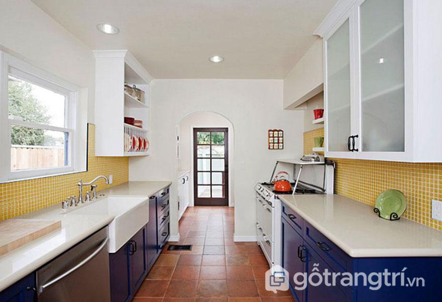 Phòng bếp kết hợp gam màu xanh hải quân, màu vàng và sàn lát gạch nung (Ảnh: Internet)