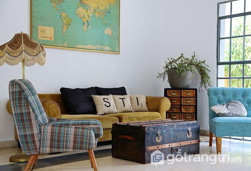 Ghế sofa hình chữ I màu vàng cam thảo trầm và chiếc hòm cũ kỹ làm bàn trà (Ảnh: Internet)