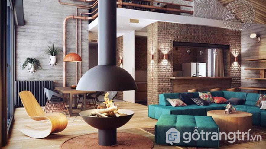 Căn phòng khách nổi bật với bức tường gạch trơ trụi, với màu xanh của ghế sofa, và màu nâu của bàn ghế (Ảnh: Internet)