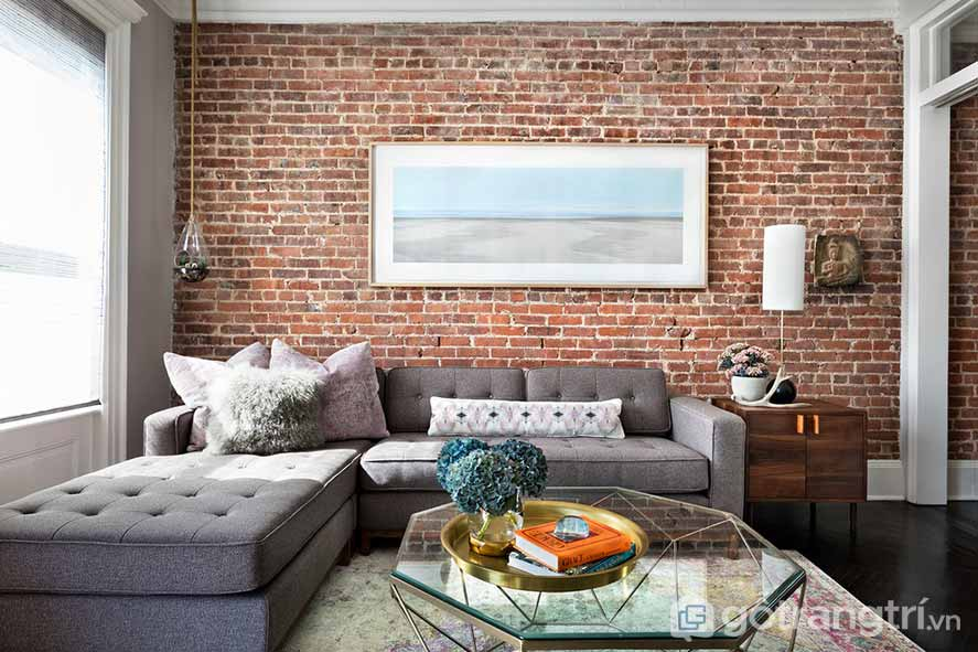Bức tranh treo tường nổi bật trên bức tường gạch đỏ rực (Ảnh: Internet)