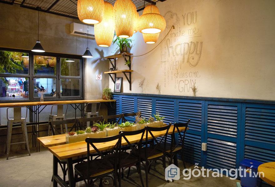Phong cách nội thất retro được thể hiện qua không gian bên trong với đèn lồng trang trí, bộ bàn ghế cao, sát cửa kính (Ảnh: Internet)