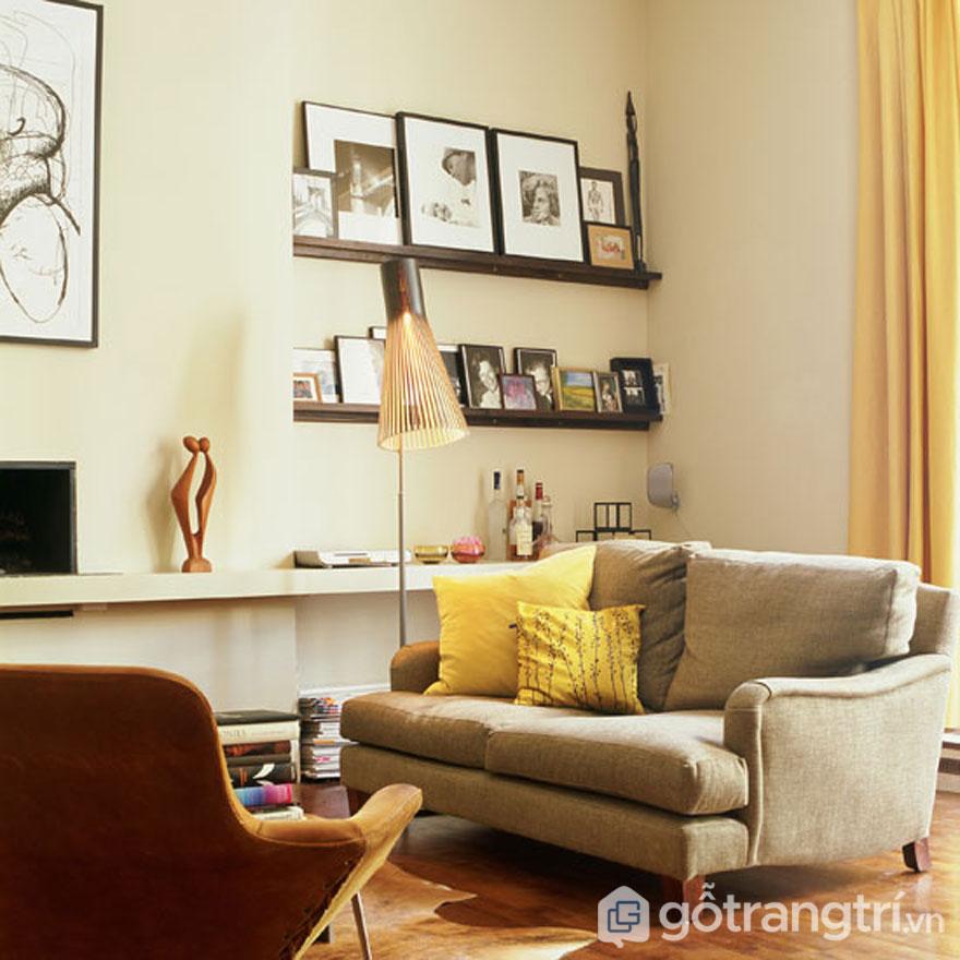 Ghế sofa màu ghi kết hợp khung ảnh cũ kĩ làm nổi bật phong cách nội thất retro ấn tượng (Ảnh: Internet)