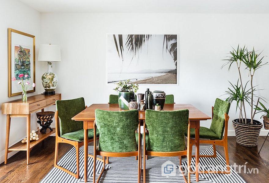 Phong cách nội thất tropical của mẫu phòng ăn này nổi bật với ghế ngồi màu xanh, với tranh tường phong cảnh đẹp mắt (Ảnh: Internet)