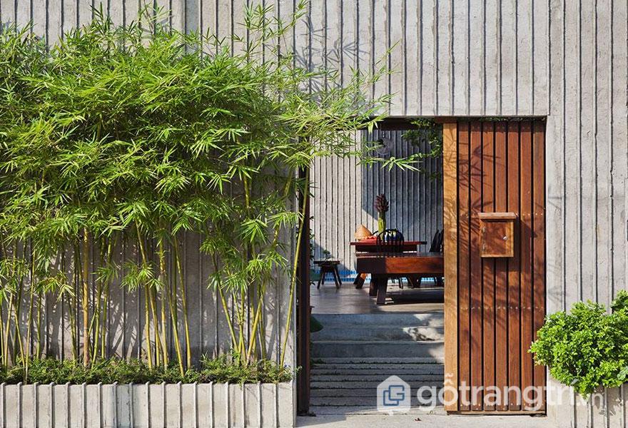 Tường sử dụng chất liệu xi măng, cửa gỗ với cây cối trồng xung quanh (Ảnh: Internet)