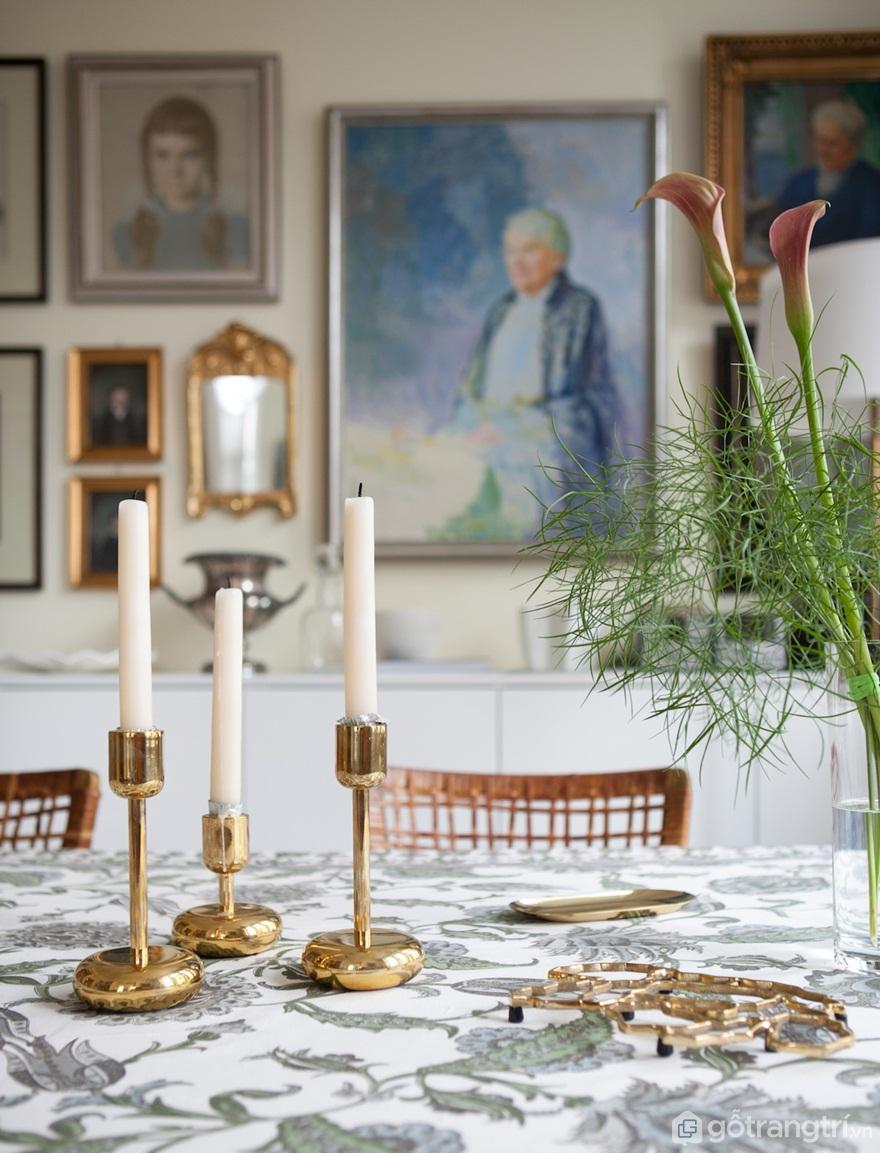 """Đồng thau và các mảnh mạ vàng có thể được tìm thấy ở đây và trong phòng ăn.Nến """"Nappula"""" củaIittalathêm ánh sáng đẹp mắt trên bàn ăn.Khăn trải bànpaisleylà một tìm thấy từIndiska(Ảnh: Internet)"""